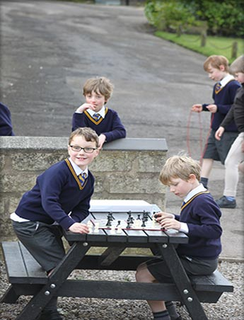 Children happily playing chess in the playground